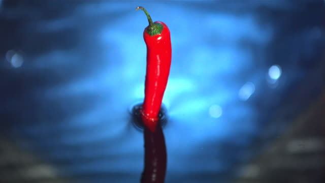 Red chili pepper falling into water video