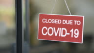 istock Red closed sign due to Covid-19 on shop window 1221353817