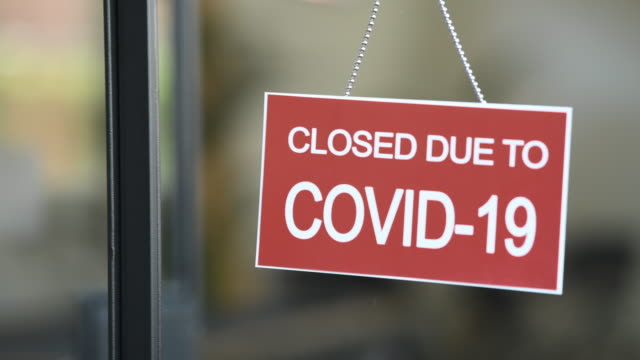 red closed sign due to covid-19 on shop window - democrazia video stock e b–roll
