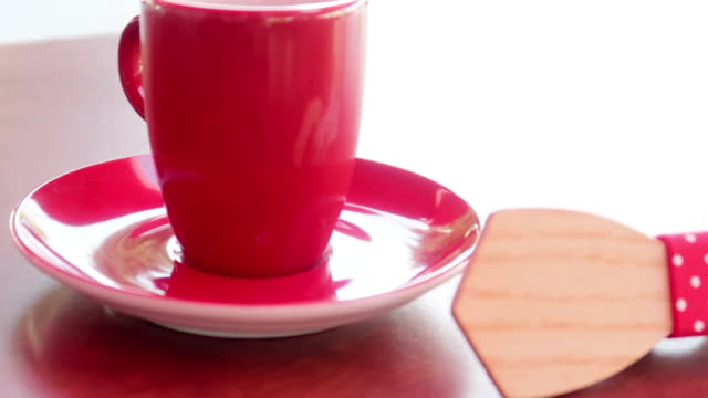 Red coffee mug on a table with elegant, wooden bow tie