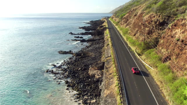 AERIAL: Red convertible driving along the picturesque coastal road