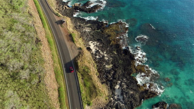 aerial: red convertible driving on beautiful coastal road above the ocean cliffs - aerial beach stock videos & royalty-free footage