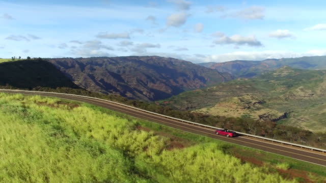 AERIAL: Red convertible driving on the edge of amazing majestic canyon in Hawaii