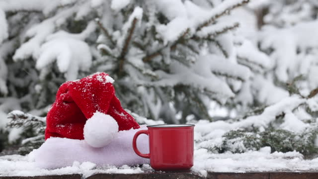 Red cup of coffee and Santa Claus hat on wooden table in snow