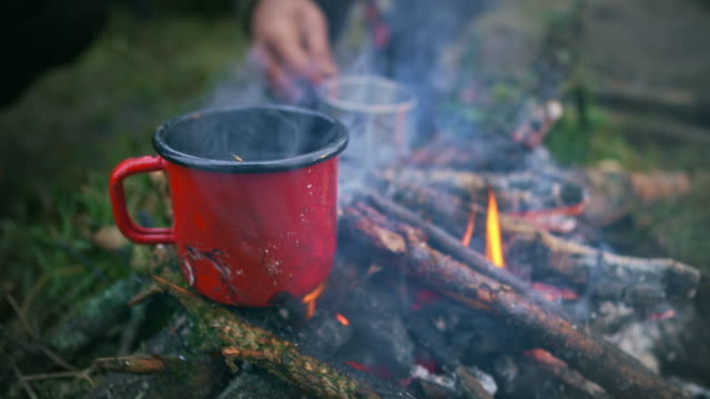 Red cup set on the twigs of the camp fire