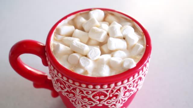 vídeos de stock, filmes e b-roll de copo vermelho com cacau e marshmallows, natal e conceito dos feriados do ano novo - chocolate quente