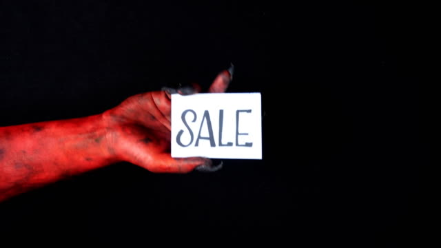Red demon hand holding sale card. 50 fps video