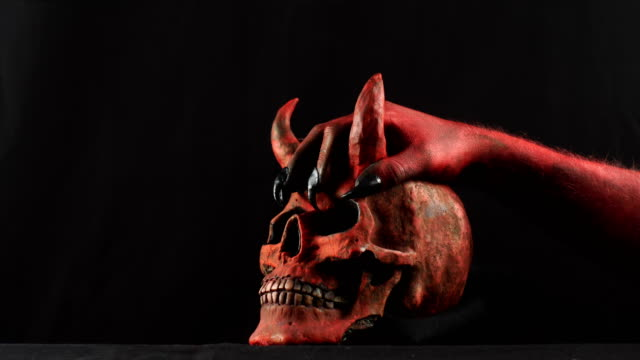 Red demon hand touching red demon skull. 50 fps video