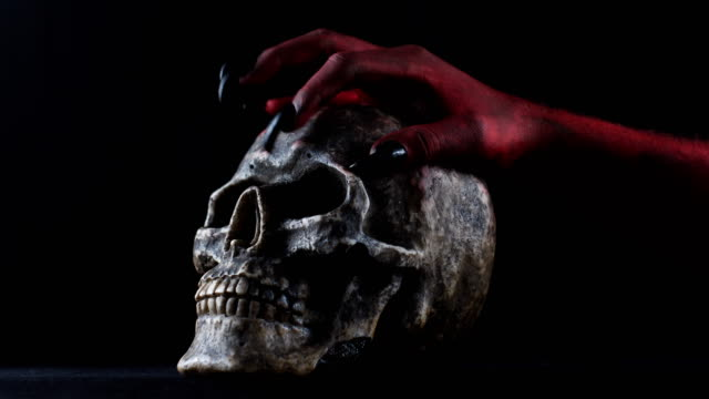 Red demon hand touching the skull. 50 fps video