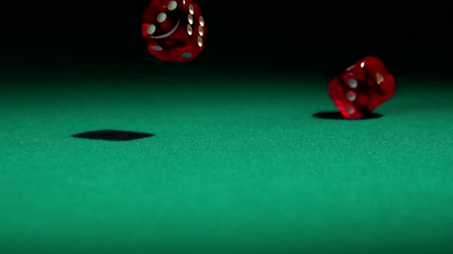 Red dice falling on the green casino table in slow-motion. video