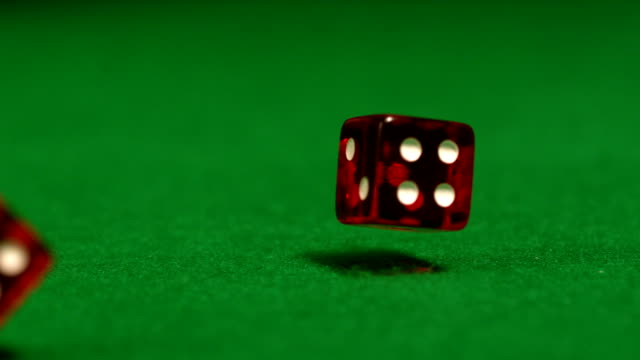 Red dice rolling on casino table video