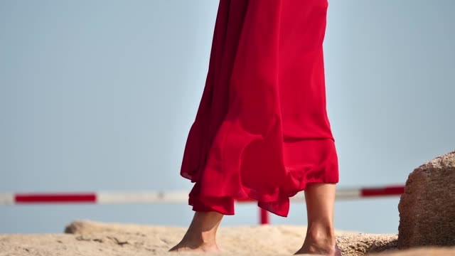 vídeos de stock e filmes b-roll de red dress flying in wind, bare foot girl standing on rock, super slow motion, romantic and beauty concept. - saia