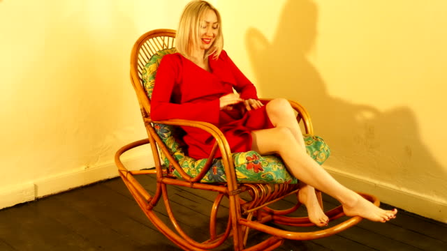 red dresses woman with rocking chair video