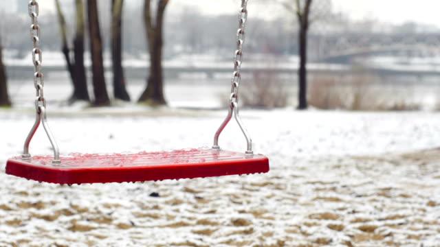 red empty swing during the winter. - chain studio bildbanksvideor och videomaterial från bakom kulisserna