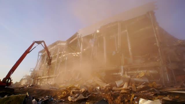 red excavator by destroyed hockey stadium in dust cloud