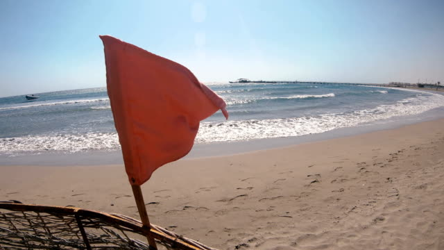 red flag hanging on the beach - proibizione video stock e b–roll