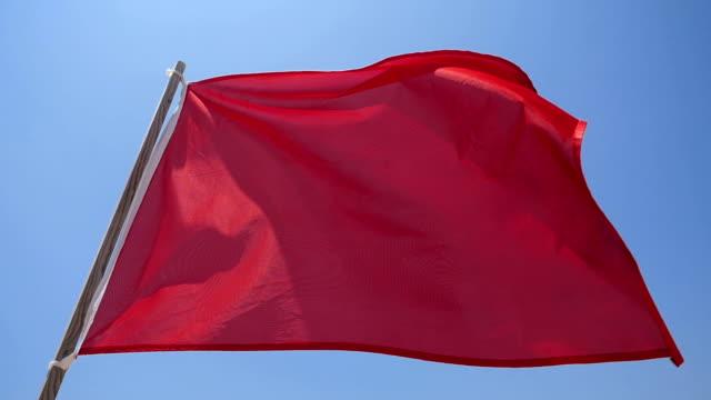 vídeos de stock, filmes e b-roll de bandeira vermelha na praia. câmera lenta. - flag