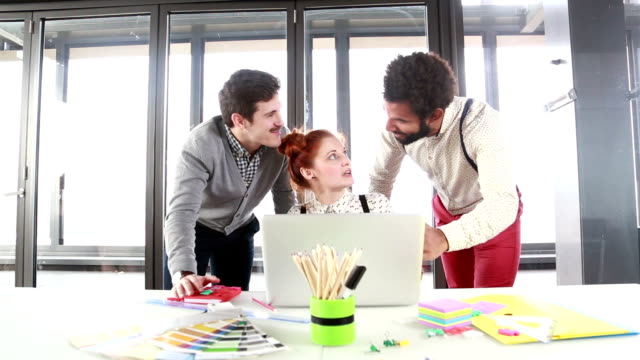 Red hair woman discussing new ideas on laptop with male colleagues video