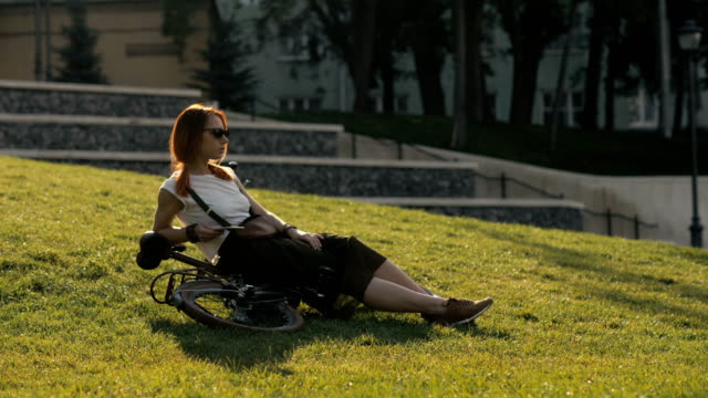 red haired woman cyclist lying on green grass in city park. woman bike park - ragazza auricolari rossi video stock e b–roll