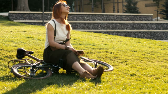red haired woman sitting on bicycle lying on grass in city park. woman bike park - ragazza auricolari rossi video stock e b–roll