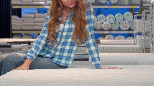 vídeos y material grabado en eventos de stock de mujer pelirroja sonriendo, sentada en un nuevo colchón ortopédico en la tienda - colchón