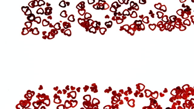 red heart shape confettis on white surface 4k - simbolo concettuale video stock e b–roll