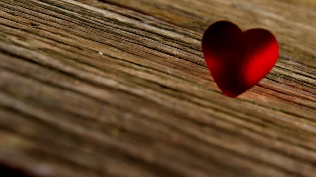 red heart tuck in the wooden plank 4k - simbolo concettuale video stock e b–roll