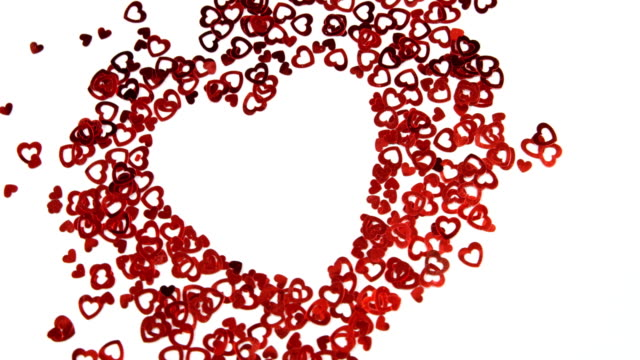 red hearts  confetti forming a heart on white surface 4k - simbolo concettuale video stock e b–roll