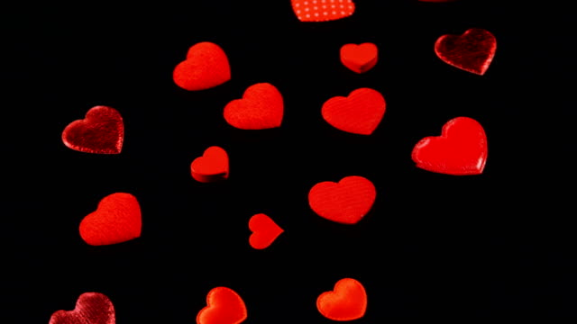 red hearts shapes falling on the black surface 4k - simbolo concettuale video stock e b–roll