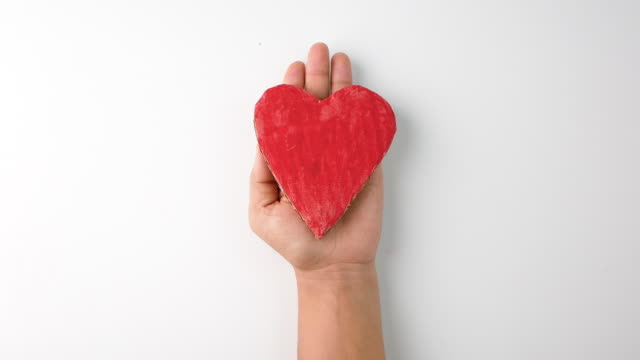A red heart-shaped cardboard placed on the hand and stretching out, isolated on white background. Concept of love and valentines day.