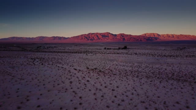 Red Hills Over Mojave Desert at Dusk - Drone Shot Drone flight over open desert near Twentynine Palms, California, with the rays of the sun still touching the hills. mojave desert stock videos & royalty-free footage