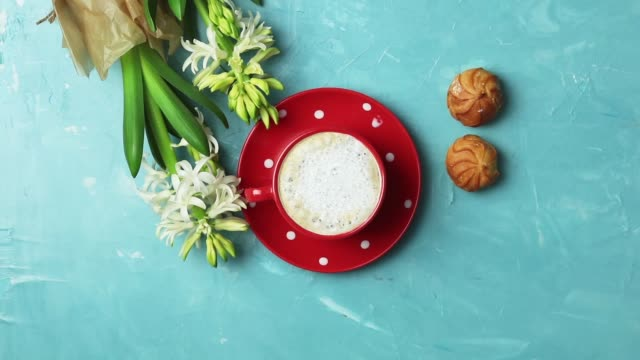 Red in white dotted cup of coffee with milk, delicious profiteroles with cream and white hyacinths on blue concrete surface background. Top view, copy space. Beautiful spring greeting card. video