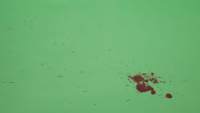 stockvideo's en b-roll-footage met rode inkt splatter over groene schermachtergrond - bespatterd