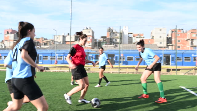 Red jersey female footballer dribbling and kicking for goal