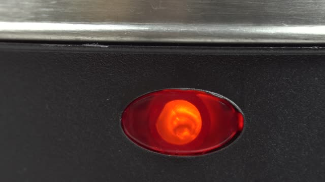 red lamp lights up when electric kettle is switched on. Macro, close-up.