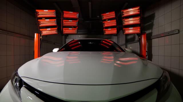 セラミックコーティングを乾燥するための赤いランプは、車の後ろにあります - 体 洗う点の映像素材/bロール