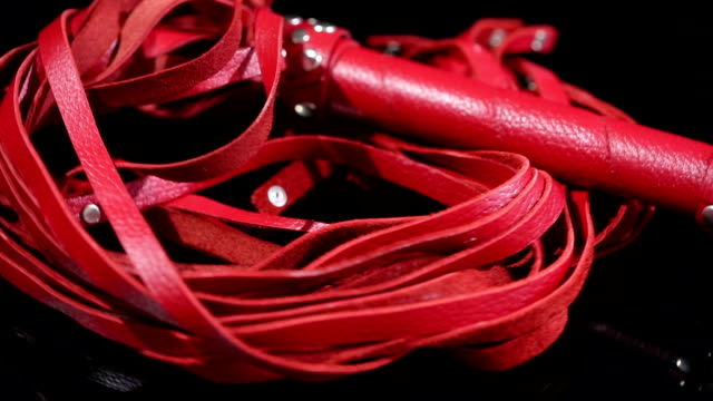 red leather whip for BDSM games. on a black background. sex toy video