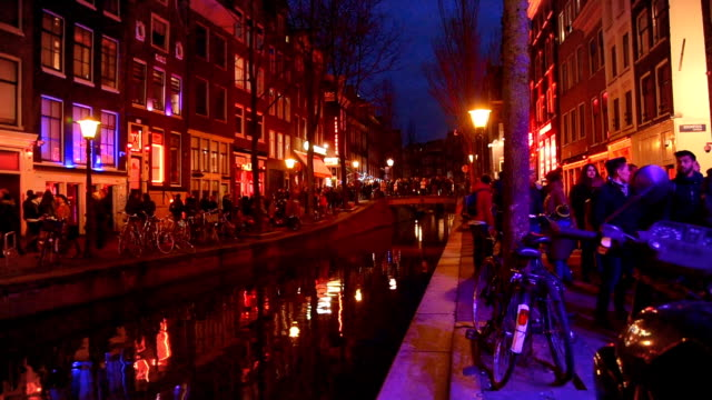 red light destrict view and amsterdam canal, bicycles and cyclists, houseboats, living boats. (ed) - amsterdam video stock e b–roll