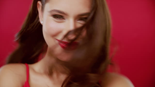 Red lipstick done right 4k video footage of a beautiful young woman having fun against a red studio background human hair stock videos & royalty-free footage