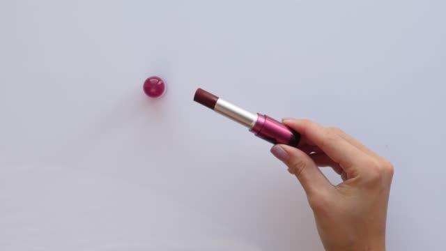stockvideo's en b-roll-footage met rode lippenstift in handen van de vrouw - lippenstift