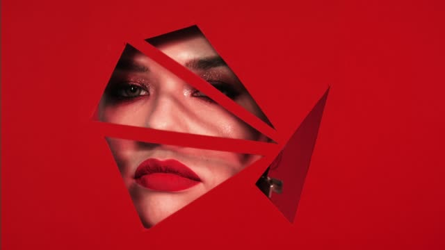 Red lipstick. Face of girl with beautiful bright make-up appears in triangular holes of red paper background. She sighs, opens her lips. Mascara with sparkles and red lipstick. Advertising female cosmetics. mascara stock videos & royalty-free footage