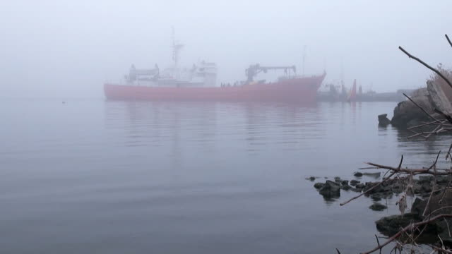 Red loading vessel on quay river in midst of morning video