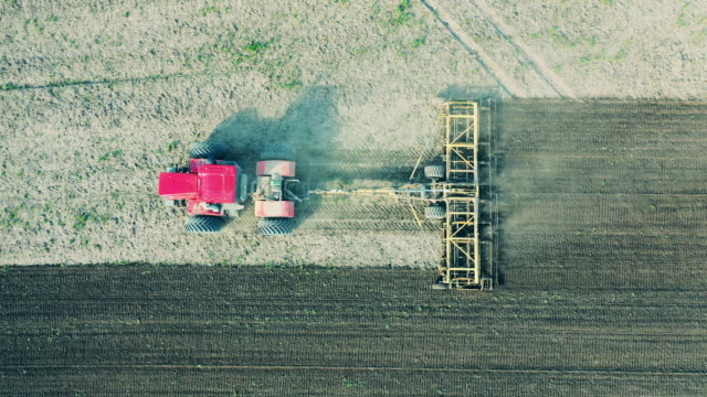 Red machine works on furrows, sows seeds. Red machine works on furrows, sows seeds. 4K agricultural occupation stock videos & royalty-free footage