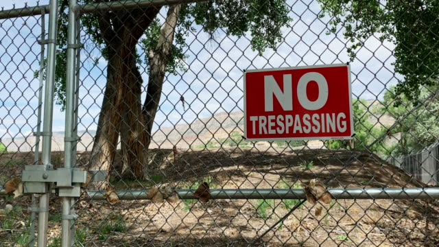 "a red ""no trespassing"" sign hanging on a locked chainlink gate guarding property on a sunny day - serratura video stock e b–roll"
