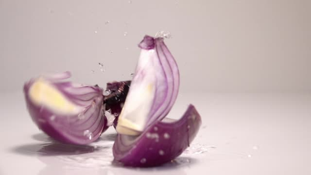 Red onion falling on water ground in slow motion on white background SlowMotion 240fps - vídeo