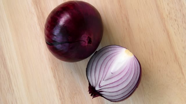 Red onion rotating top view on wooden background Red onion rotating top view on wooden background red onions stock videos & royalty-free footage