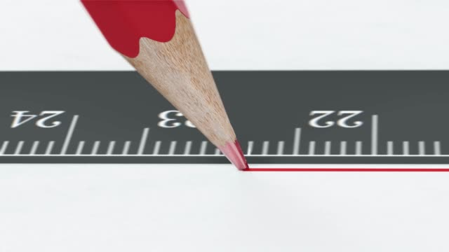 Red pencil draws a line along the ruler