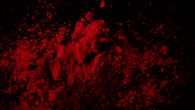 Red pepper powder drops down. Slow motion, top view A large amount of paprika red powder drops down on the black table. Slow motion, top view spice stock videos & royalty-free footage