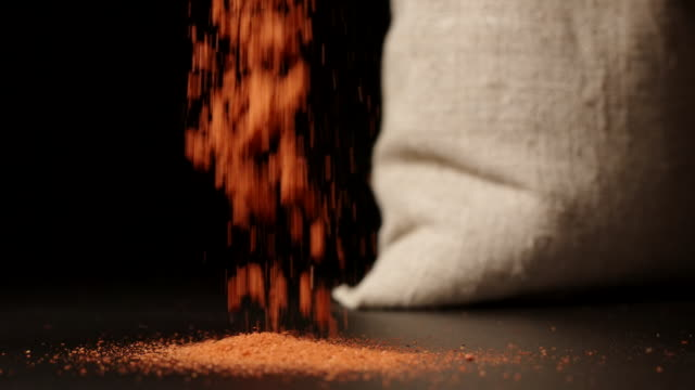 SLOW MOTION: Red pepper powder falling down near a sac SLOW MOTION: Red pepper powder falling down near a sac sac stock videos & royalty-free footage