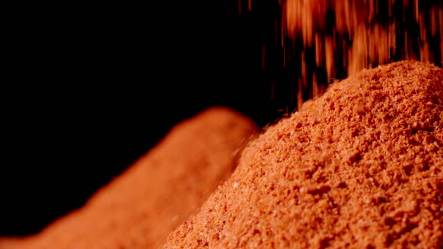 polvere di peperone rosso che cade in un mucchio su un tavolo - paprica video stock e b–roll